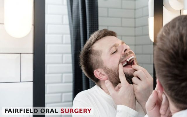 Man looking at a missing tooth in the mirror - Fairfield, CA